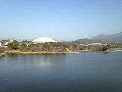 Kayoichoike_Pond_and_Kasuya_Town_Gymnasium_from_footbridge_on_west_side_of_Kayoicho_Park